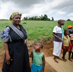 Dudu stands with her son, Mlamuli, who is sponsored. Zinhle, in white pants, stands to the right.