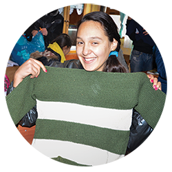 Girl holds a donated sweater.