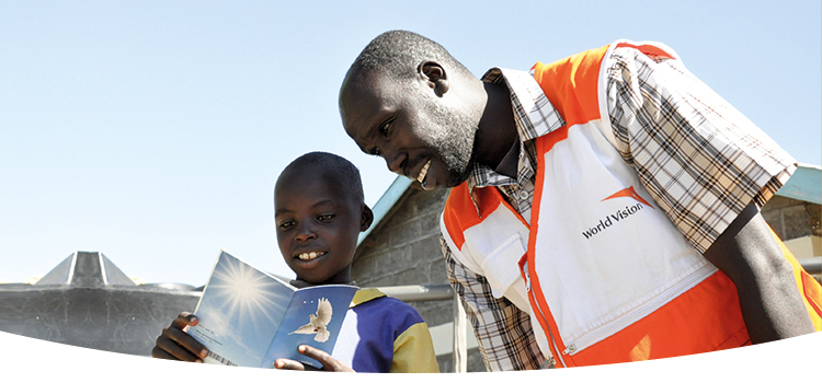 World Vision employee is reading a book with a boy.