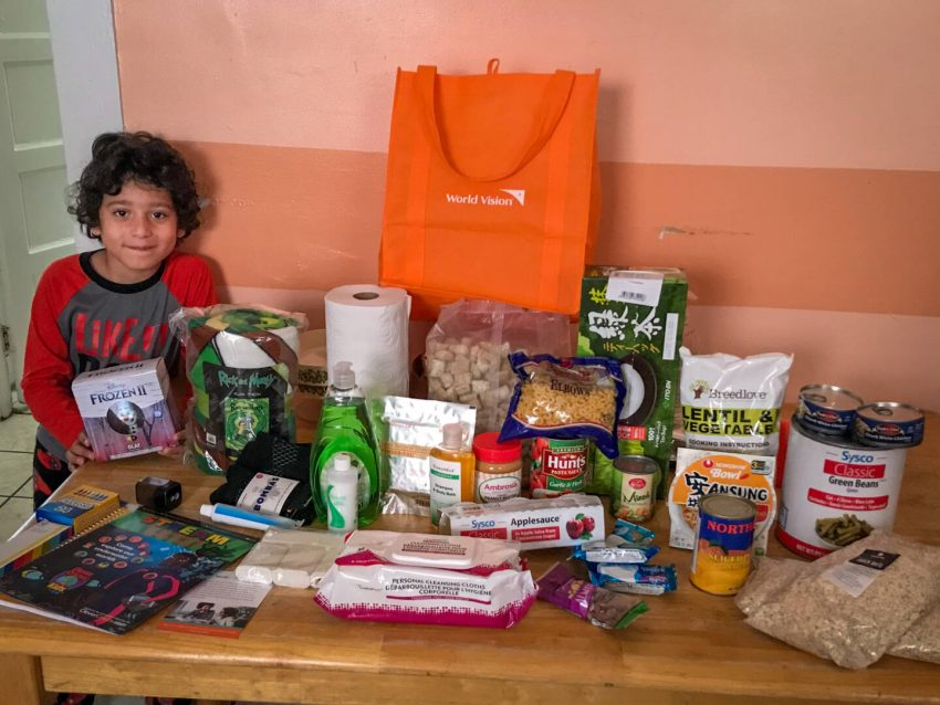 Six-year-old Ahni stands next to a table filled with supplies from World Vision Family Emergency Kits.