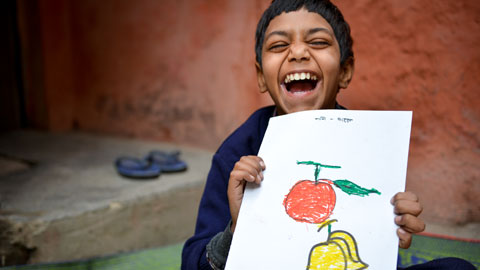 How it works to sponsor a child. Step 1, Choose a child to sponsor, like this little boy in India. Bedal age 9, proudly holds a drawing.