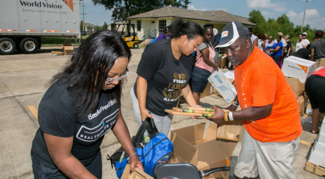 World Vision's Antonio Evans, right, and volunteers help distribute relief supplies to local families impacted by flooding Sept. 2 at the Greater Antioch Full Gospel Baptist Church in Baton Rouge, La. (©2016 Kathy Anderson/Genesis Photos)