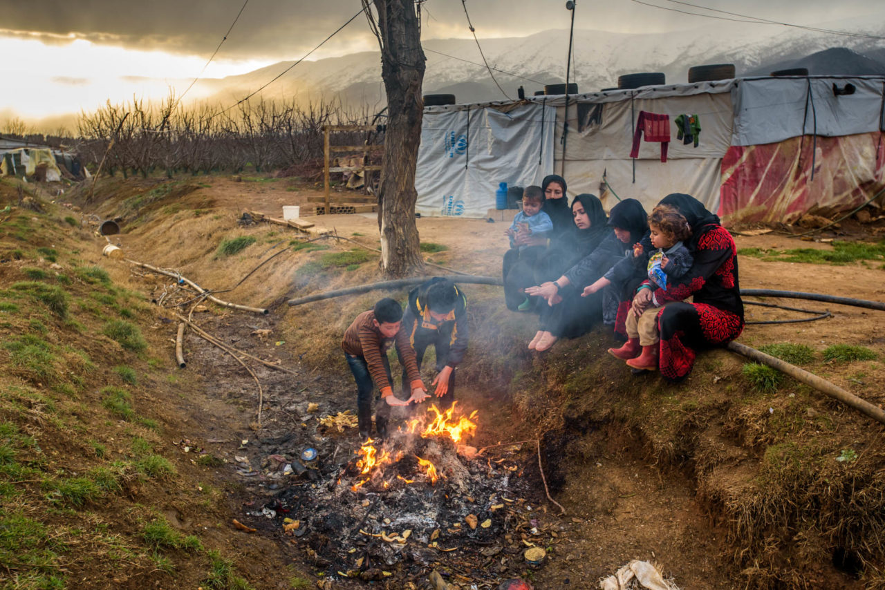 A family gathers around a small fire of burning trash at the edge of a tent settlement.