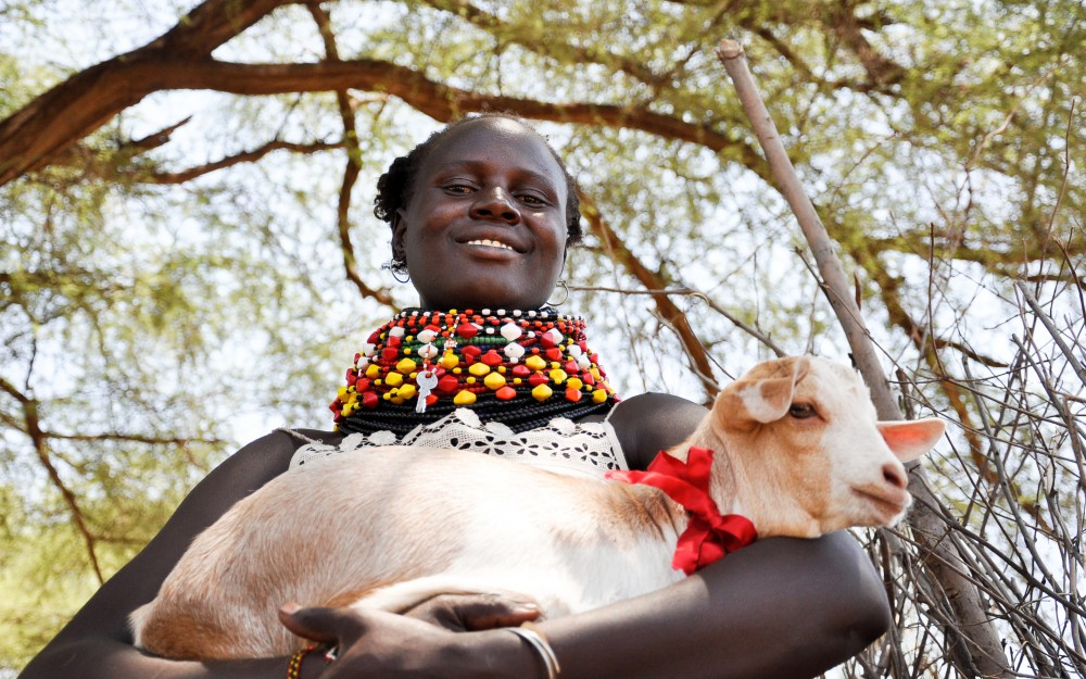 Mary Arupe, 30, a mom of three in Kenya, holds one of the six Galla goats she received from a donation to World Vision's Gift Catalog.