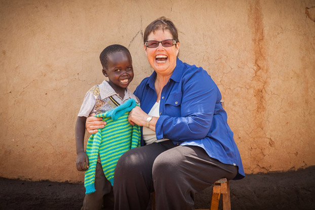 Debbie Macomber gifts a hand-knitted sweater to Josiah, age 8, in World Vision's Marich Pass community in Kenya. (Photo: 2014 Lindsey Minerva/World Vision)