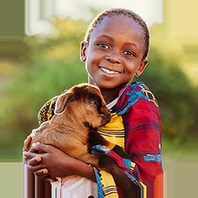 An african boy holds a goat.