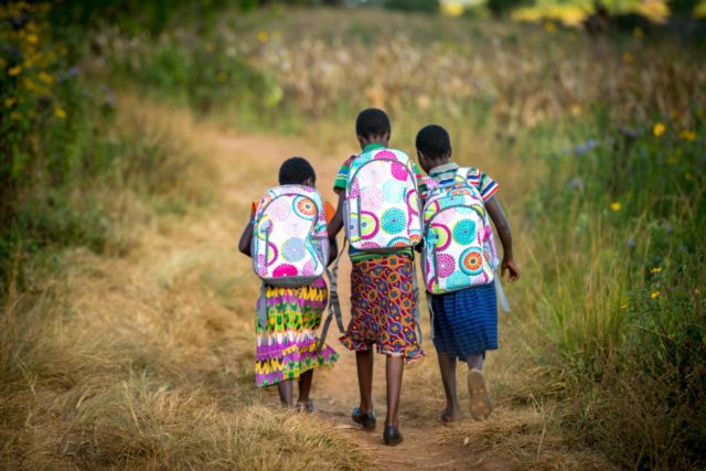 Zambian girls walk to school wearing new backpacks from World Vision.