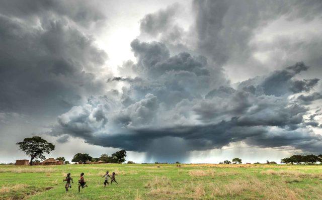 Children run across a field as stormy cumulonimbus clouds pour rain to a village in Magoye, Zambia.