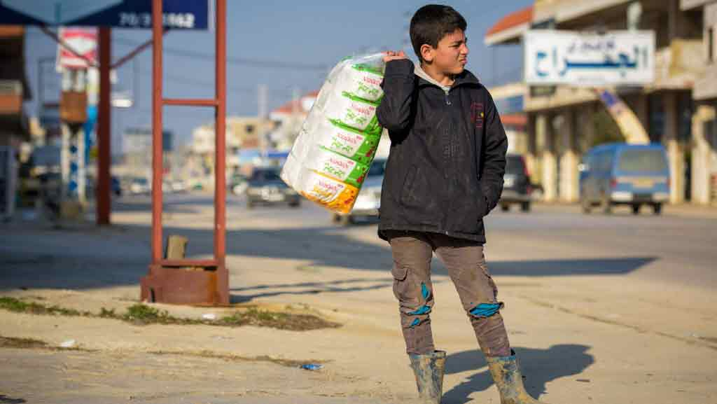 Ali, a Syrian refugee boy in the Bekaa Valley of Lebanon, sells tissues on the busy Beirut-to-Damascus road. The sole wage-earner of his family, he makes at most 4 USD a day, which goes toward rent and other family expenses. He is often harassed as he stands on the roadside. He and his family live in Rajab Informal Tented Settlement. Ali works to support the family and doesn't attend school.