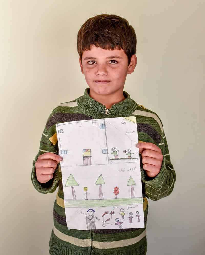 Yahia shows his drawing.