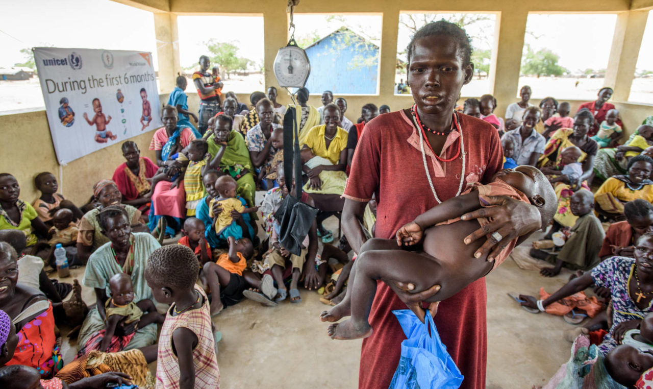 A mother holds her severely malnourished baby among dozens of others visiting a clinic in Kuajok,SouthSudan, where World Vision runs an outpatient therapy program.Communities here have struggled with food insecurity for years since the conflict began, but some areas are now experiencing or on the brink of famine. (©2015 World Vision/photo by Jon Warren)