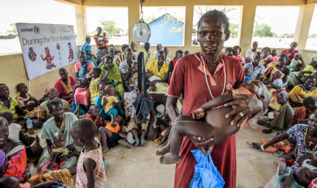 A mother holds her severely malnourished baby among dozens of others visiting a clinic in Kuajok, South Sudan, where World Vision runs an outpatient therapy program. Communities here have struggled with food insecurity for years since the conflict began, but some areas are now experiencing or on the brink of famine. (©2015 World Vision/photo by Jon Warren)