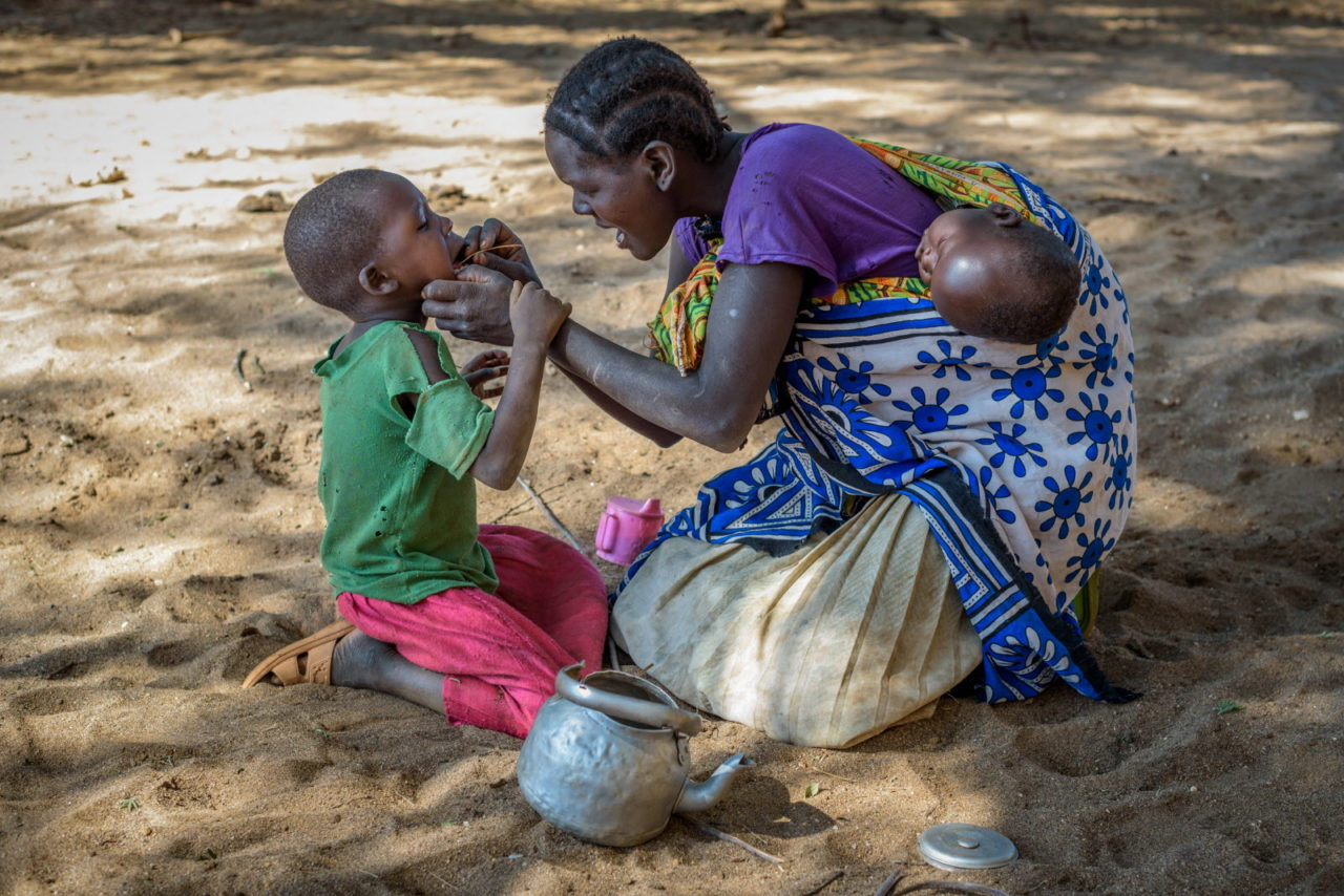 Monica uses a twig to clean Cheru's teeth in a break from their long walk for water.