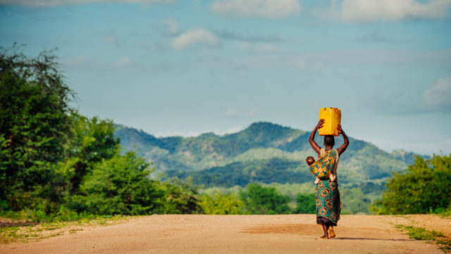 A woman in Sinazongwe Zambia, carries a baby on her back and container of water from a World Vision borehole on her head. Carrying water long distances can have lasting effects on one's health, some research shows. (©2016 World Vision/photo by Jon Warren)