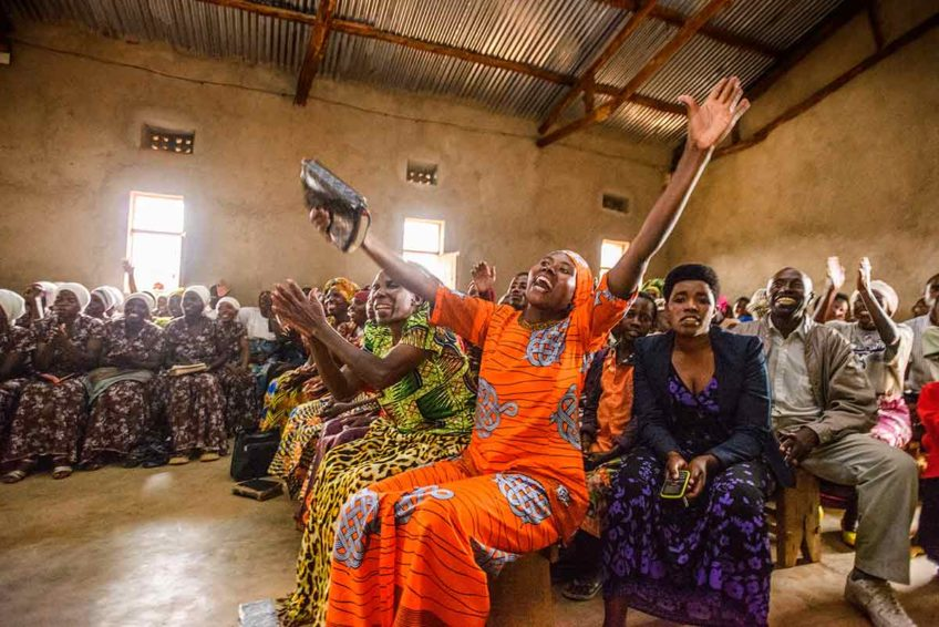 Photos of praise and worship from around the world - a woman in a church in Rwanda waves her hands enthusiastically