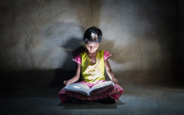 Education around the world, going to school. Little girl in India sits on the floor with a book