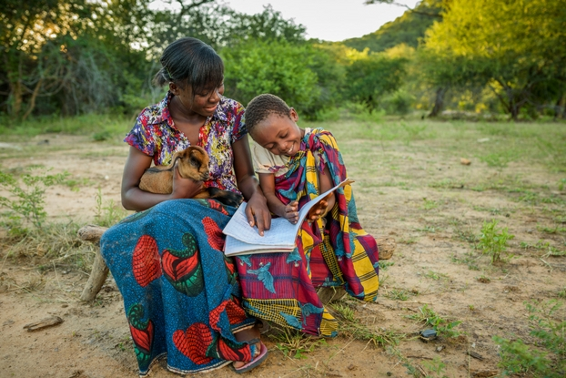 Modester—and one of her baby goats—helps her cousin Evelyn with school work. (Photo: ©2016 World Vision/photo by Jon Warren)
