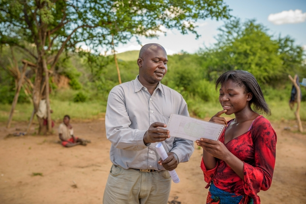 Seth Siamugande looks over Modester's amazing exam results. (Photo: ©2016 World Vision/photo by Jon Warren)