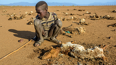 9-year-old Ejiem sits with the carcass of his favorite sheep, Merireng, in Turkana, Kenya. The East Africa drought has caused the death of many animals like Merireng. (©2017 World Vision/photo by Jon Warren)