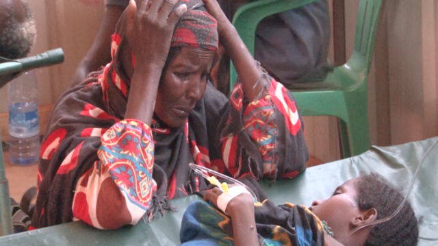 A grandmother in Somalia looks on with worry as her young grandchild is treated for watery diarrhea.