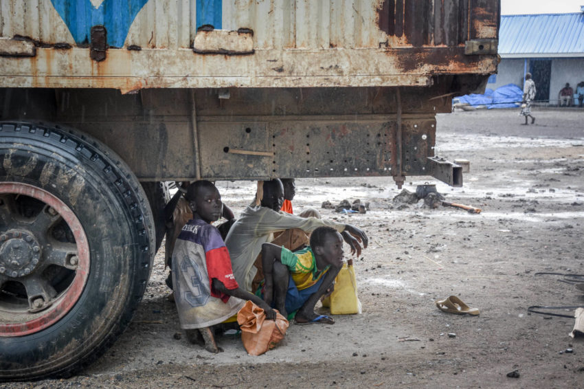 South Sudanese boys sit under the back of an aid truck, taking cover from the rain.