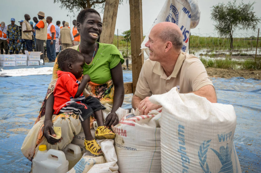 A white man talks with a South Sudanese mother and her toddler at a food distribution.