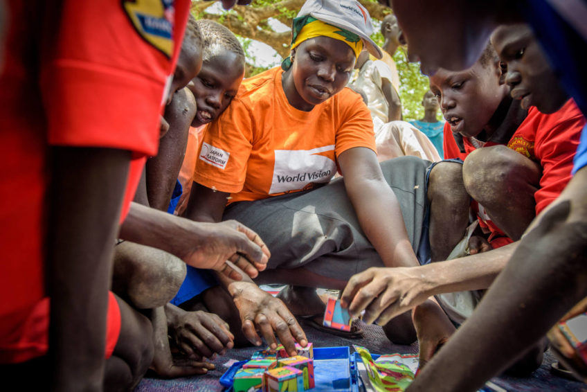 World Vision staff woman plays games with South Sudanese children.