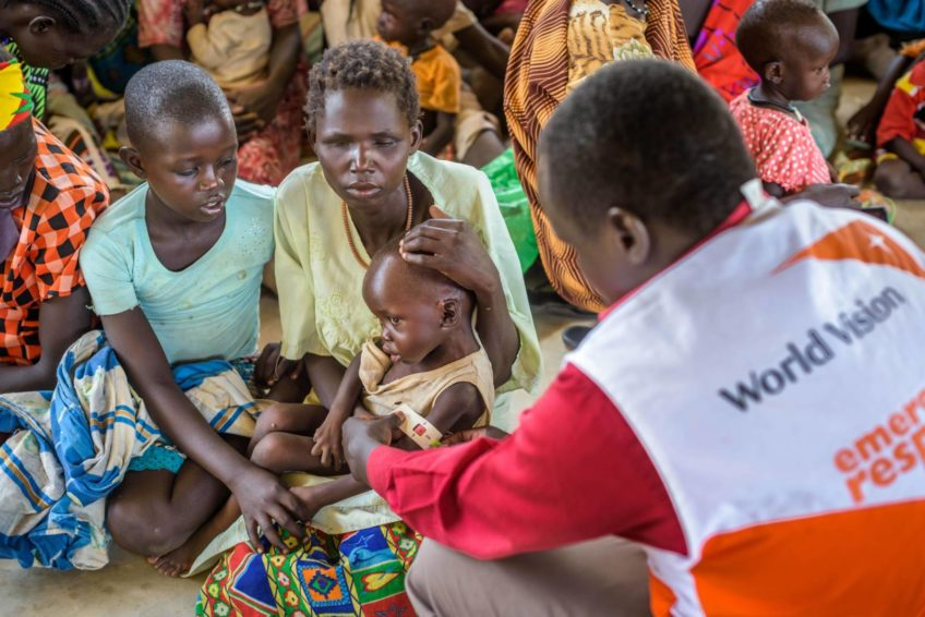 World Vision staff measure the upper arm circumference of a malnourished toddler sitting in her blind mother's lap. Beside them sits a concerned older sister, looking at the young child.