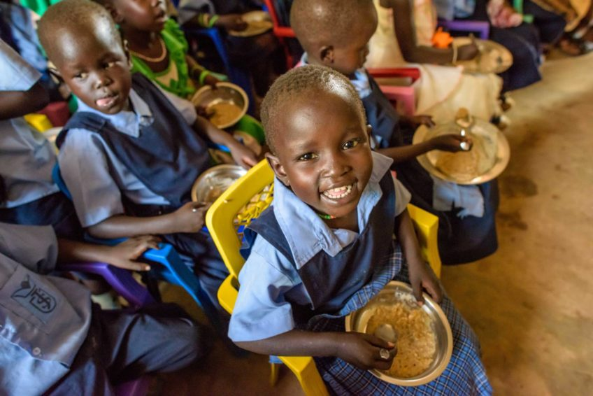 A happy student is eating a bowl of nutritious porridge in a classroom.