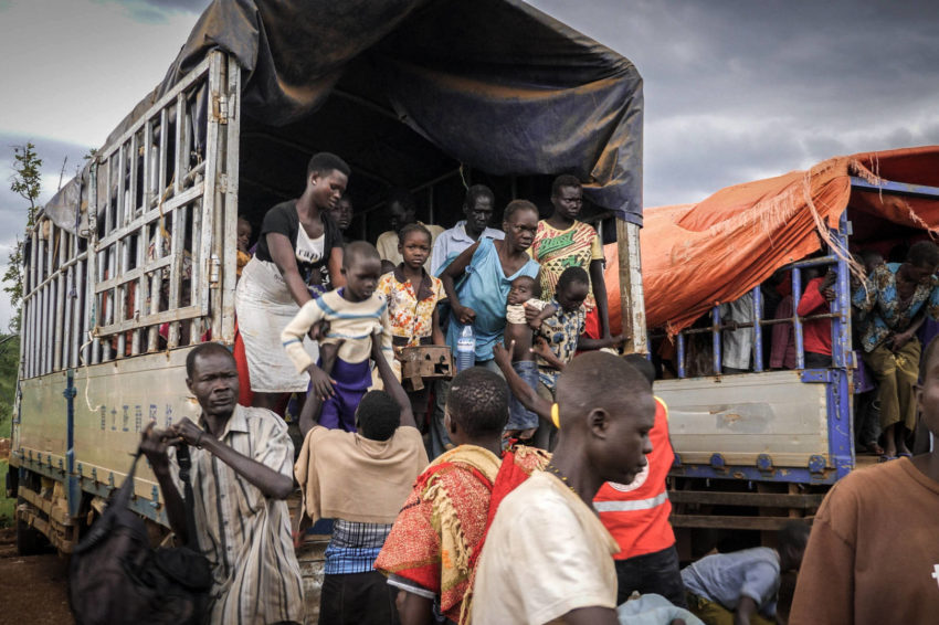 South Sudan Refugees climb out of the back of a huge truck as they arrive at the Uganda border.