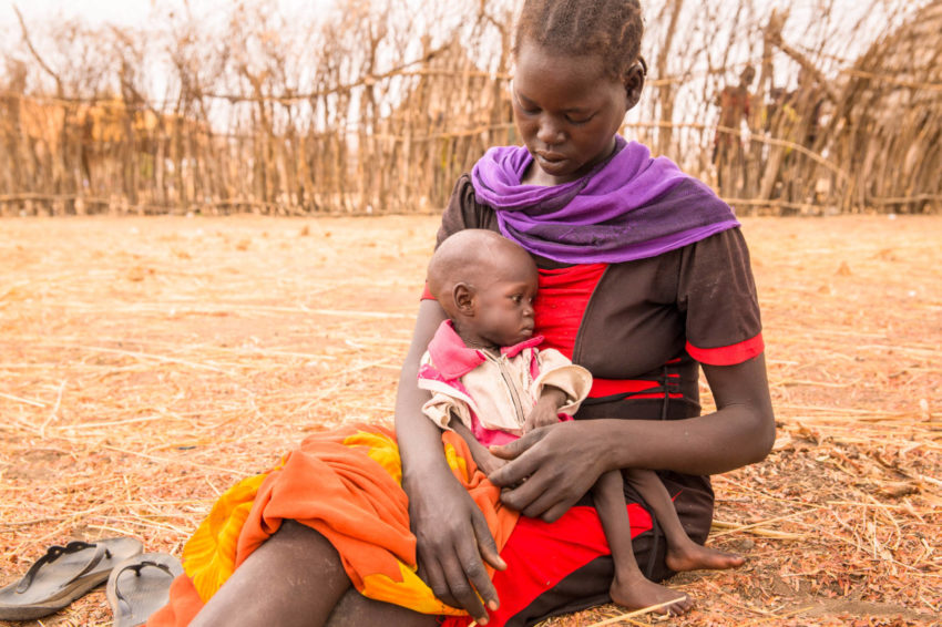 A mother cradles her skinny, severely malnourished baby in her lap while sitting on the ground.