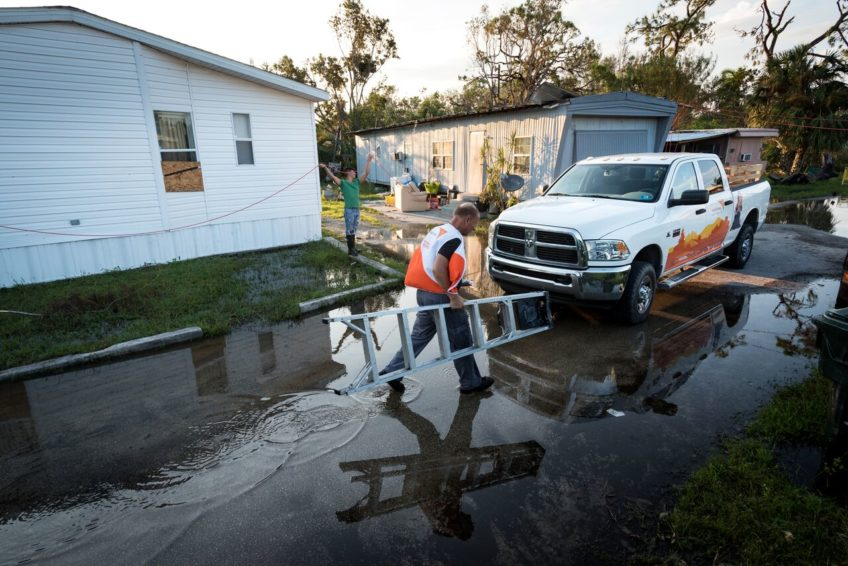 Rich Mozeanko, carrying ladder, is a member of World Vision's global rapid response team that brought relief goods and other assistance to families in Immokalee, Fla., affected by Hurricane Irma. A week after the storm, nearly 8,000 of 12,000 residential power customers were still without electricity. It could be weeks before service is restored to the hard-hit Collier County community. Many families live in trailer parks in low-lying areas with nowhere for water to drain. (©2017 World Vision/photo by Eugene Lee)