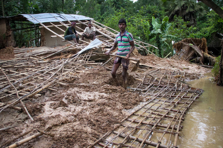 In northern Bangladesh, a man begins clearing away mud and debris from his plot of land. His home was destroyed by flooding. (©2017 World Vision/photo by Jamaal Uddin)