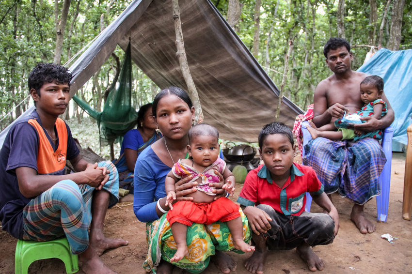 The family of World Vision registered children (available for sponsorship but not having a sponsor yet), sought safety on higher ground and waited as floodwaters receded in a makeshift shelter on the side of a road. World Vision provided bed nets, tarpaulins, food, and clean water. (©2017 World Vision/photo by Jamaal Uddin)