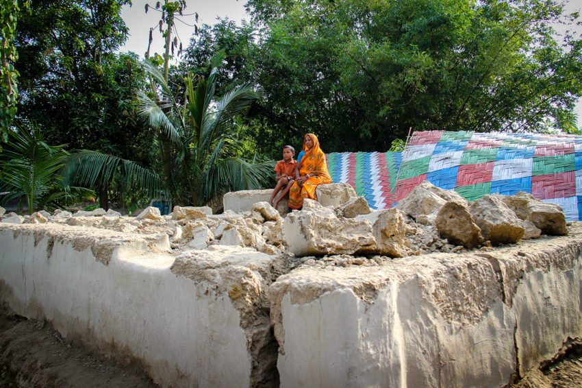 "Fulbari, Dinajpur district: Ador, a World Vision registered child (available for sponsorship but not having a sponsor yet), and his mother, Dipti Rani, sit on the foundation of their home, which was swept away by flooding. ""We cannot live like this. But we don't have money to rebuild our house,"" says Dipti. Ador misses the shelter from the warm sun: ""I feel very hot here. I want to live again in the house we had a few days ago."" (©2017 World Vision/photo by Himaloy Joseph Mree)"