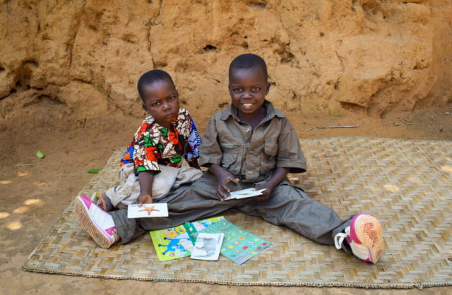 Sponsored boy Jean de Dieu (right) plays with his brother with the toys sent by his sponsor.