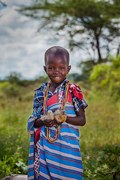 A young boy in Kenya holds baby chicks.