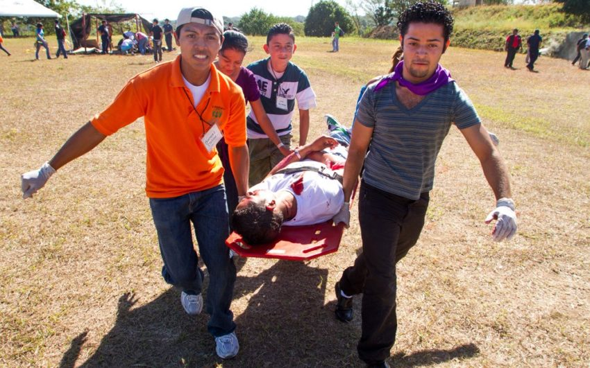 Youth carry a mock victim to an ambulance during disaster response training exercise.