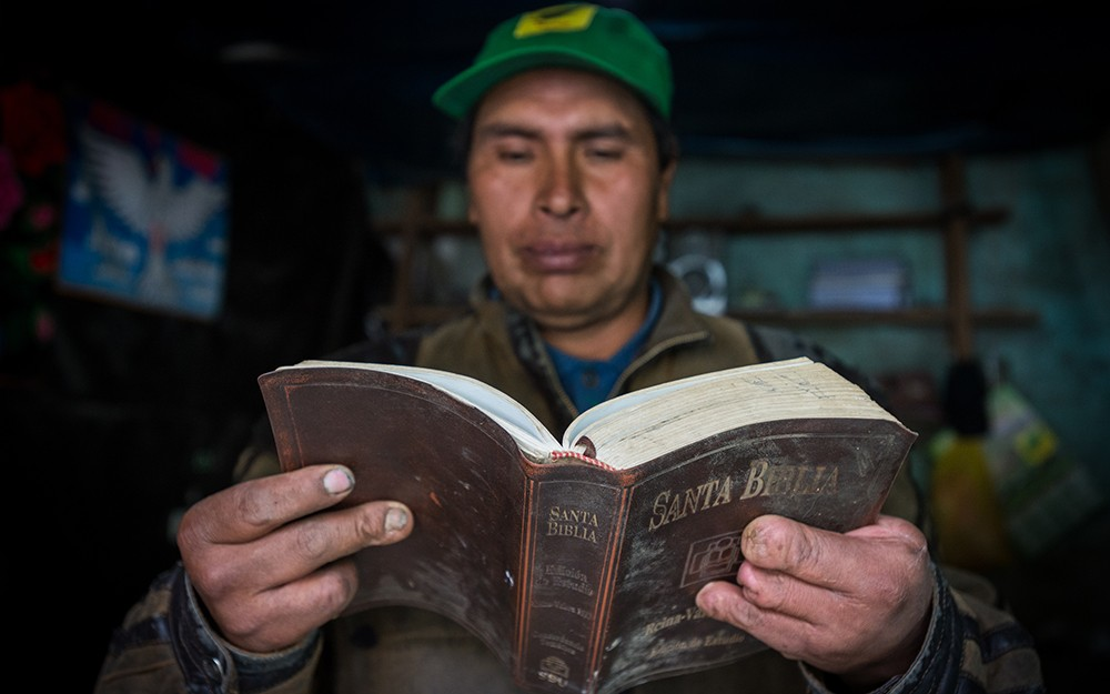 With missing or damaged fingers, a man holds a Bible in Peru.