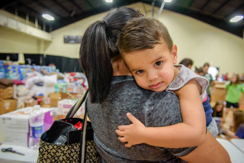 Pedro Jimenez's wife, Nuris Laviera, holds their 2-year-old son, JuanDavid. The family came to a distribution of relief supplies at Parkway Fellowship Church in Katy, Texas, in the aftermath of Hurricane Harvey. (©2017 World Vision/photo by Laura Reinhardt)