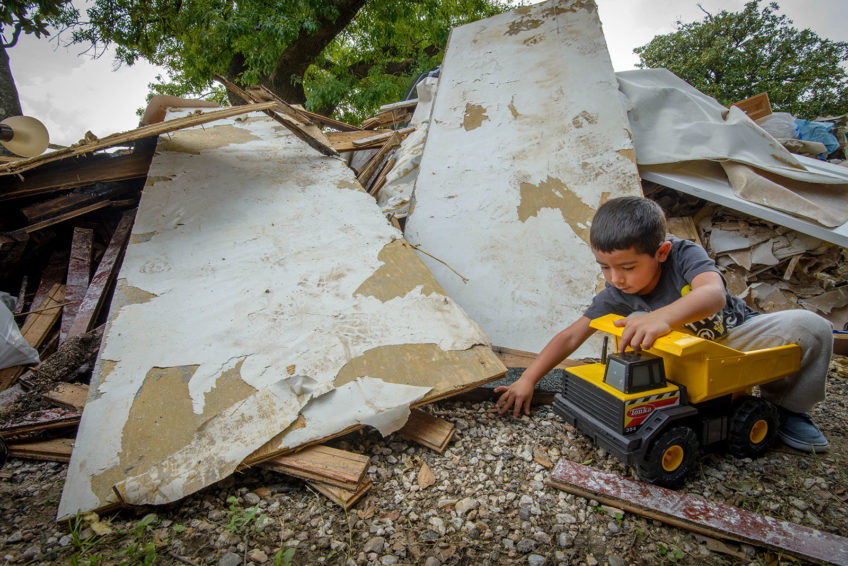 Five-year-old Vincent Miniel found one truck that wasn't destroyed by Hurricane Harvey's floodwaters. But much of the front yard is filled with debris from the house, so there's not a lot of room to play. (©2017 World Vision/photo by Laura Reinhardt)