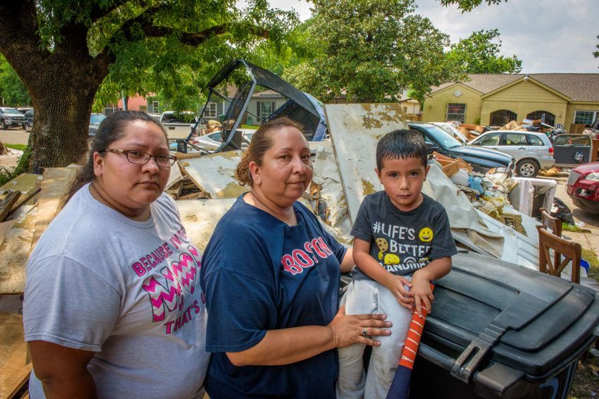 Vincent Miliel, right, and his mom, Crystal Rodriguez, left, just moved in with her mom, Linda Rodriguez, center, and her husband. Then Hurricane Harvey flooded their entire neighborhood. Now all up and down their street, houses have floodwater — destroyed debris piled high in their front yards just like that behind Vincent. (©2017 World Vision/photo by Laura Reinhardt)