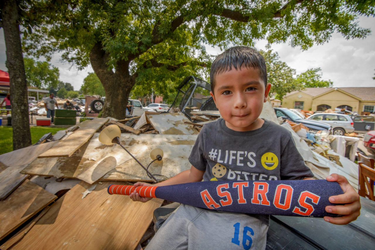 Five-year-old Vincent Miniel found a toy bat that wasn't destroyed by Hurricane Harvey's floodwaters. But much of the front yard is filled with debris from the house, so there's not a lot of room to play. (©2017 World Vision/photo by Laura Reinhardt)