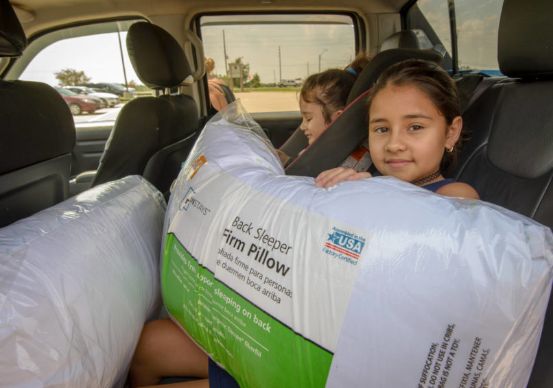 Valerie Orellana, 10, came with her family to Parkway Fellowship Church following Hurricane Harvey to pick up relief supplies. She sits in the back of the truck--filled with relief supplies--holding a pillow, which was one of the many donations World Vision was able to provide to the church. (©2017 World Vision/photo by Laura Reinhardt)