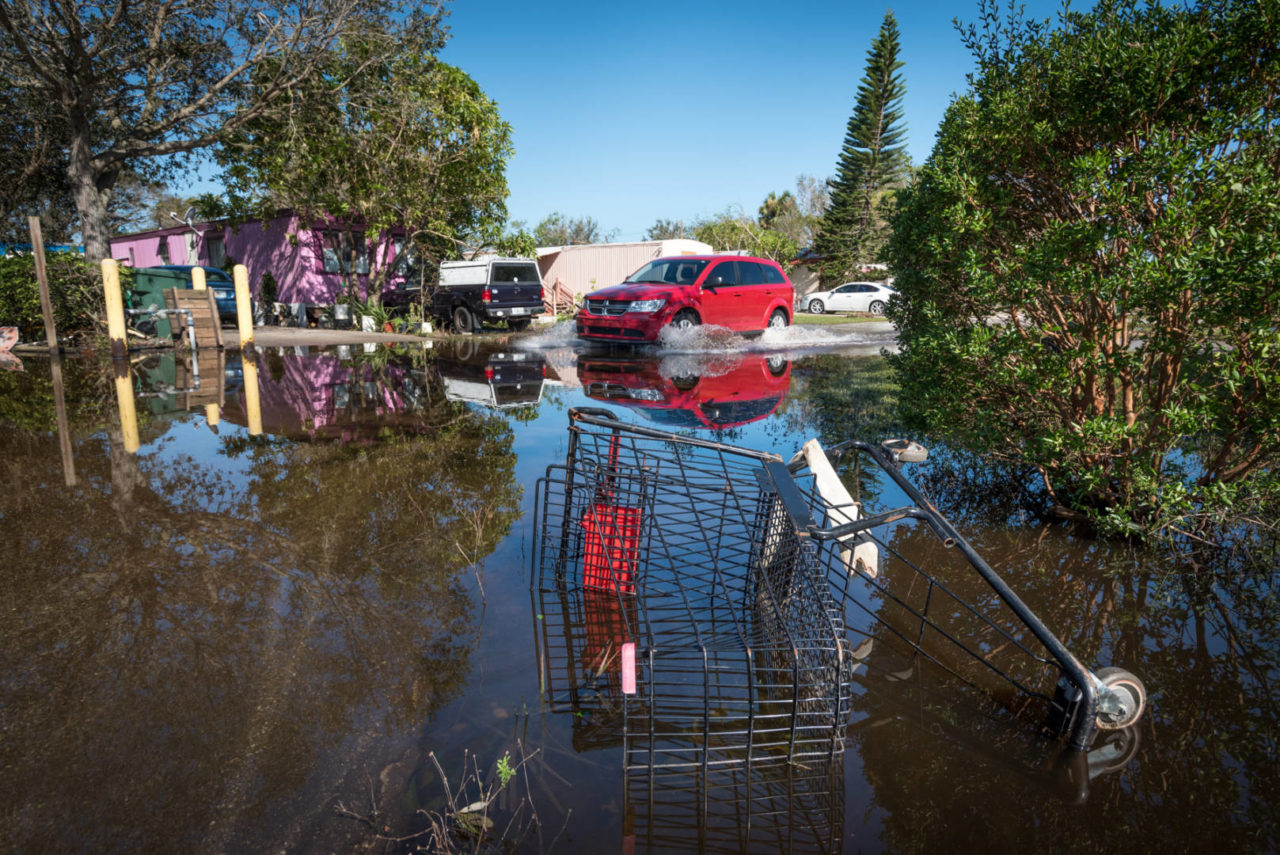 A car drives through a still-flooded area of a neighborhood in Immokalee, Fla. Sept. 13. (©2017 World Vision/photo by Eugene Lee)