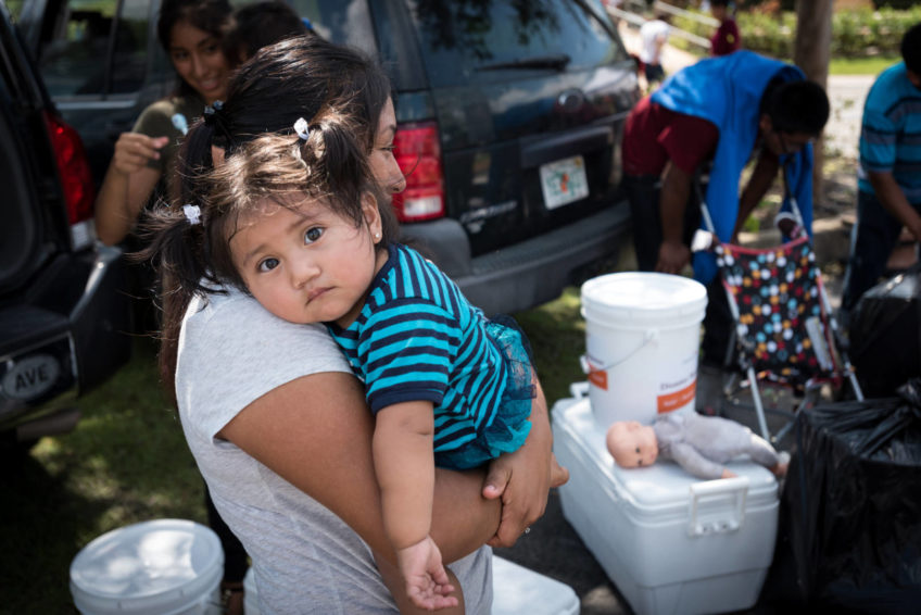 A baby waits with her mother as they load relief supplies they received from World Vision and Bethel Assemblies of God Church into a vehicle Sept. 14 in Immokalee, Fla. (©2017 World Vision/photo by Eugene Lee)