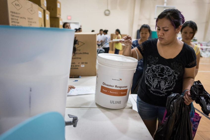 A woman picks up a storm clean-up kit while collecting relief supplies at a distribution for Hurricane Irma survivors at Bethel Assemblies of God Church in Immokalee, Florida, Sept. 14.