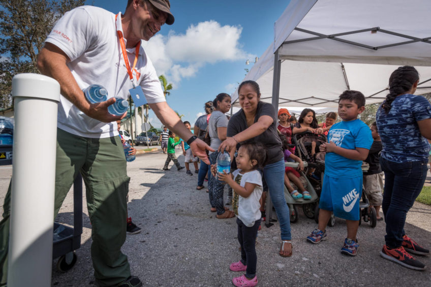James Orlando, a member of World Vision's Global Rapid Response Team, gives water to a little girl during a relief supplies distribution for Hurricane Irma survivors Sept. 14 at Bethel Assemblies of God Church in Immokalee, Florida.