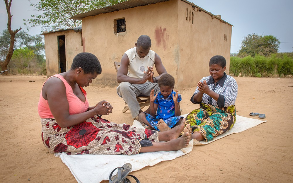 A caregiver prays with a family in Zambia.