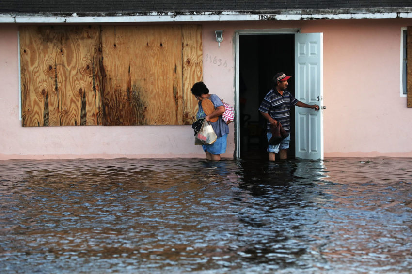 A couple leave their flooded home the morning after Hurricane Irma swept through the area on Sept. 11 in Bonita Springs, Florida. (©2017 World Vision/photo by Spencer Platt, Getty Images)